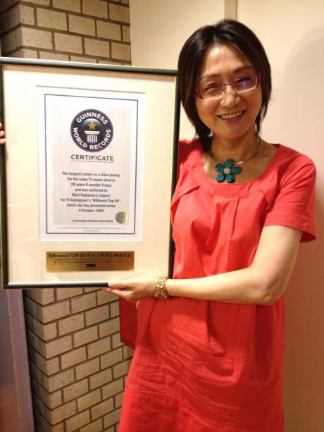 ギネス世界記録認定書を掲げる「Billboard TOP40」のVJ中村真理さん