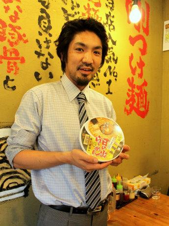 カップ麺を手にする「日の出らーめん」統括店長の横田晃一さん