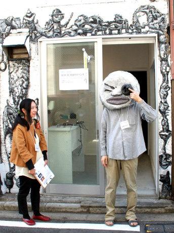 ミエテルノゾム君に変身したアーティストの照沼敦朗さん(写真右、「八番館」前)