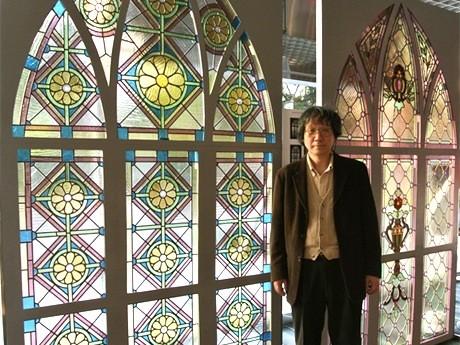 平山健雄さんと幅1.5m、高さ2.7mのステンドグラス。菊の花と幾何学模様に赤い花の模様の2作品。