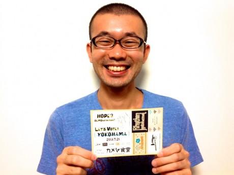 「選挙や政治を、日々の暮らしのなかで語れるきっかけにしたい」と、特典ステッカーを掲げる峰尾亮平さん