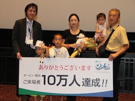 オービィ横浜館長の田井村勉さんと10万人目の来館者となった北原尚子さん一家