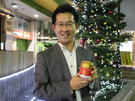 クリスマスコーヒーを手にするキーコーヒーの磯田義尊さん