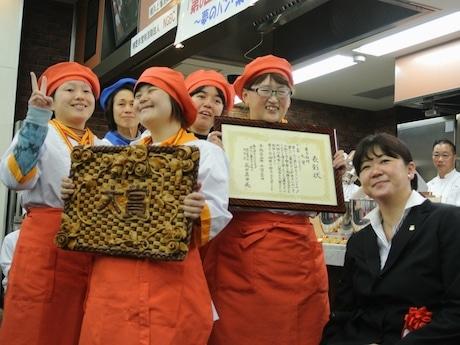 菓子部門で優勝したシンフォニー(埼玉県)とチャレンジドカップ実行委員長の成田真由美さん。表彰チームには飾りパンやケンミックス、薄力粉なども贈られた