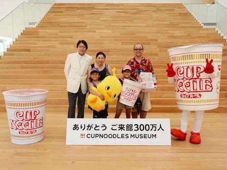 300万人目となった佐藤巧くん(左から2番目)とカップヌードル ミュージアム筒井之隆館長(左端)
