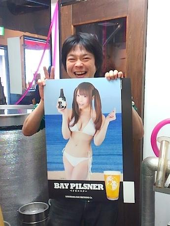 横浜ベイブルーイング代表の鈴木真也さん。「ベイピルスナー」ポスターには巨乳アイドルグループ「KNU」の南菜々子さんを起用した