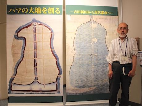 吉田新田開墾前図と開墾図を前に説明する展示担当の斉藤司さん