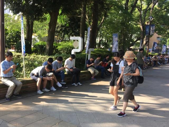 24日夕刻に横浜公園入口の日陰でポケモンGOを楽しむ人たち