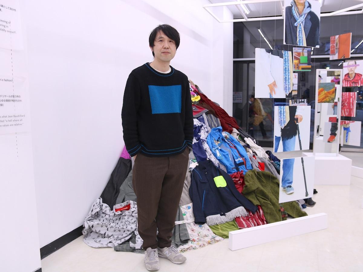 ファッションデザイナーの矢内原充志さん。会場には約100着の服が山積みに、約70着が宙吊りになっている