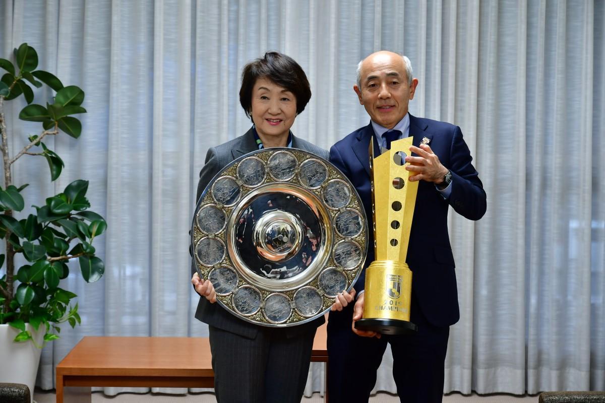 シャーレを持つ横浜市林市長とトロフィーを持つ横浜F・マリノス黒沢良二社長。