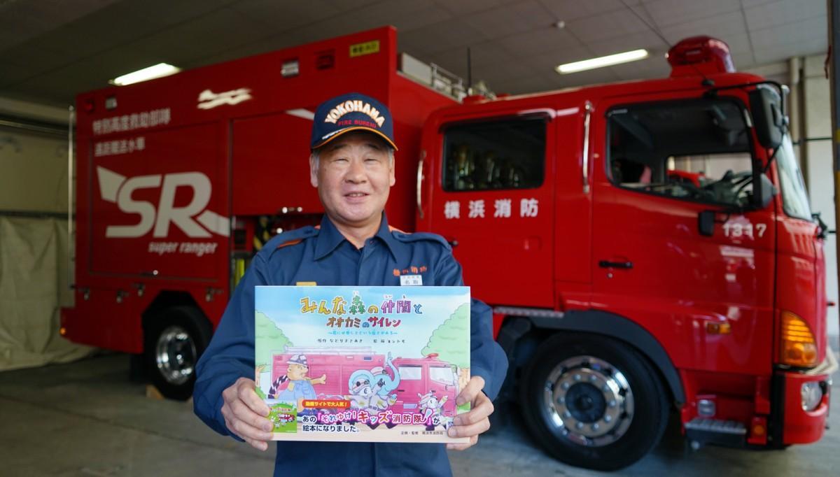 絵本を手にする原作者、元戸塚消防署長、現在は消防局予防部予防部長の名取正暁さん