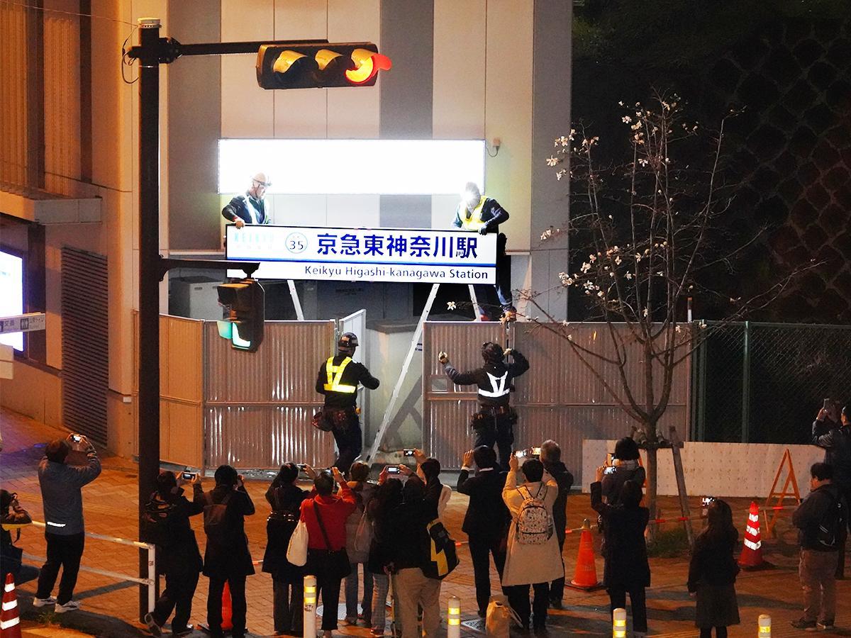 仲木戸の駅名看板を「京急東神奈川」に架け替える様子。同駅では5月10日までの期間限定で外壁に看板が1枚追加された