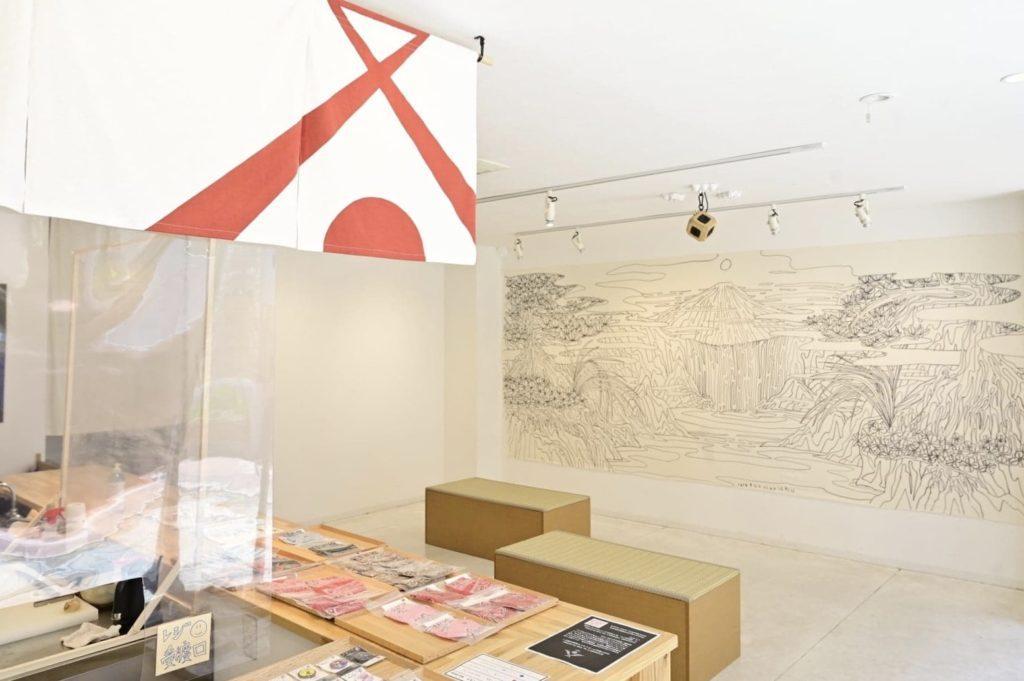 開放的な店内にはアーティストの作品が並ぶ。右の壁には狩集広洋さんの作品。