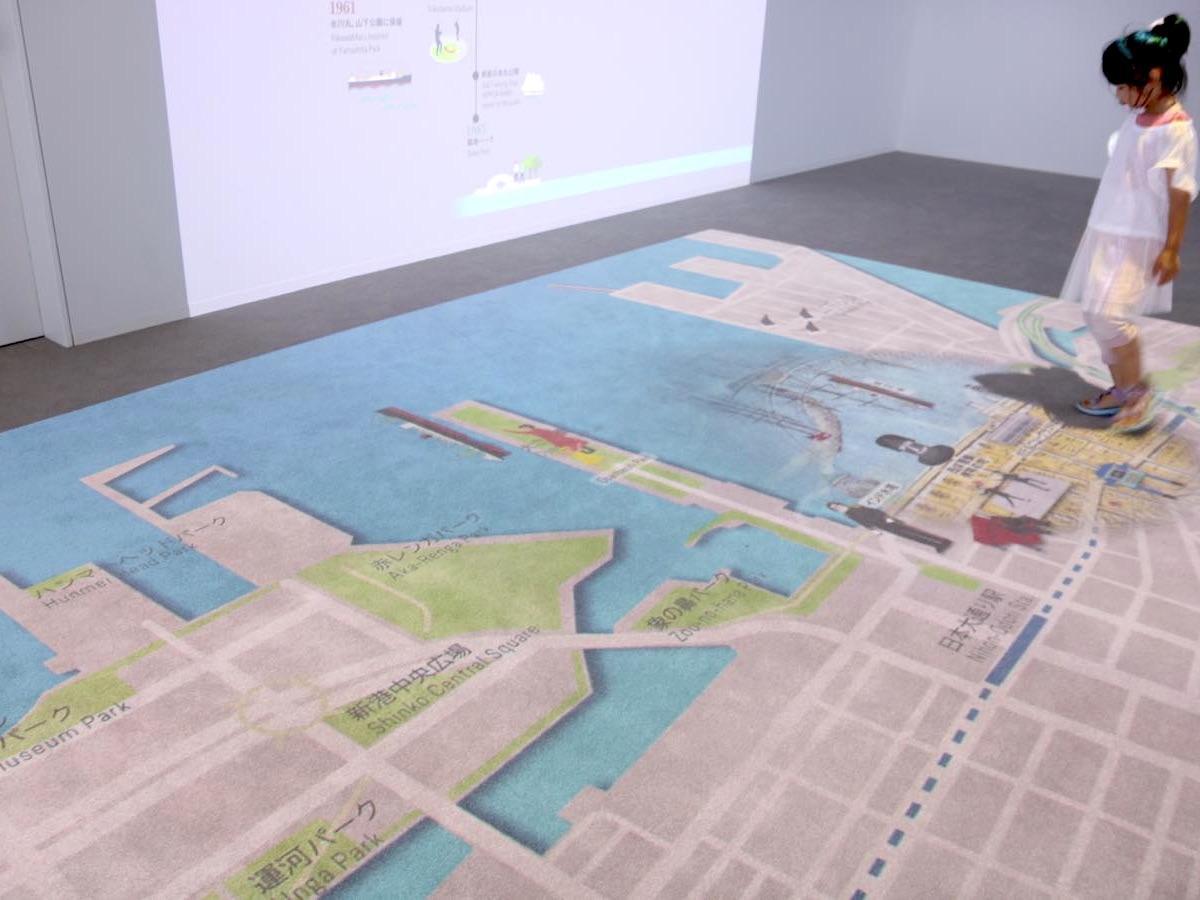 床に投影されたインタラクティブマップに足を踏み入れると、観光スポットやモチーフ、昔の地図が浮かび上がる。地図は開港前、開港後(1870年)、居留地時代(1880年)、震災復興期(1933年)のものを使用