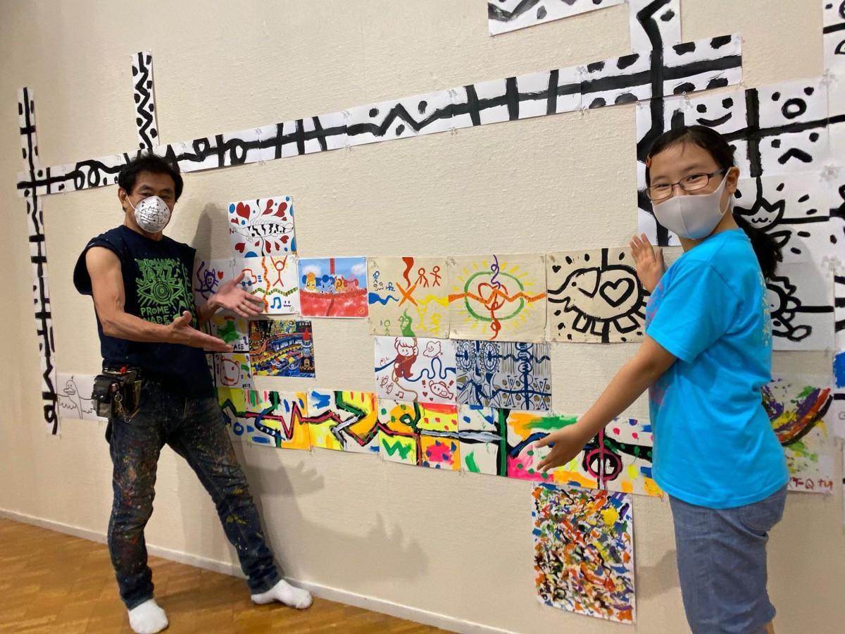 ロコサトシさん(左)と、絵本の創作に取り組む中学1年生の花怜さん
