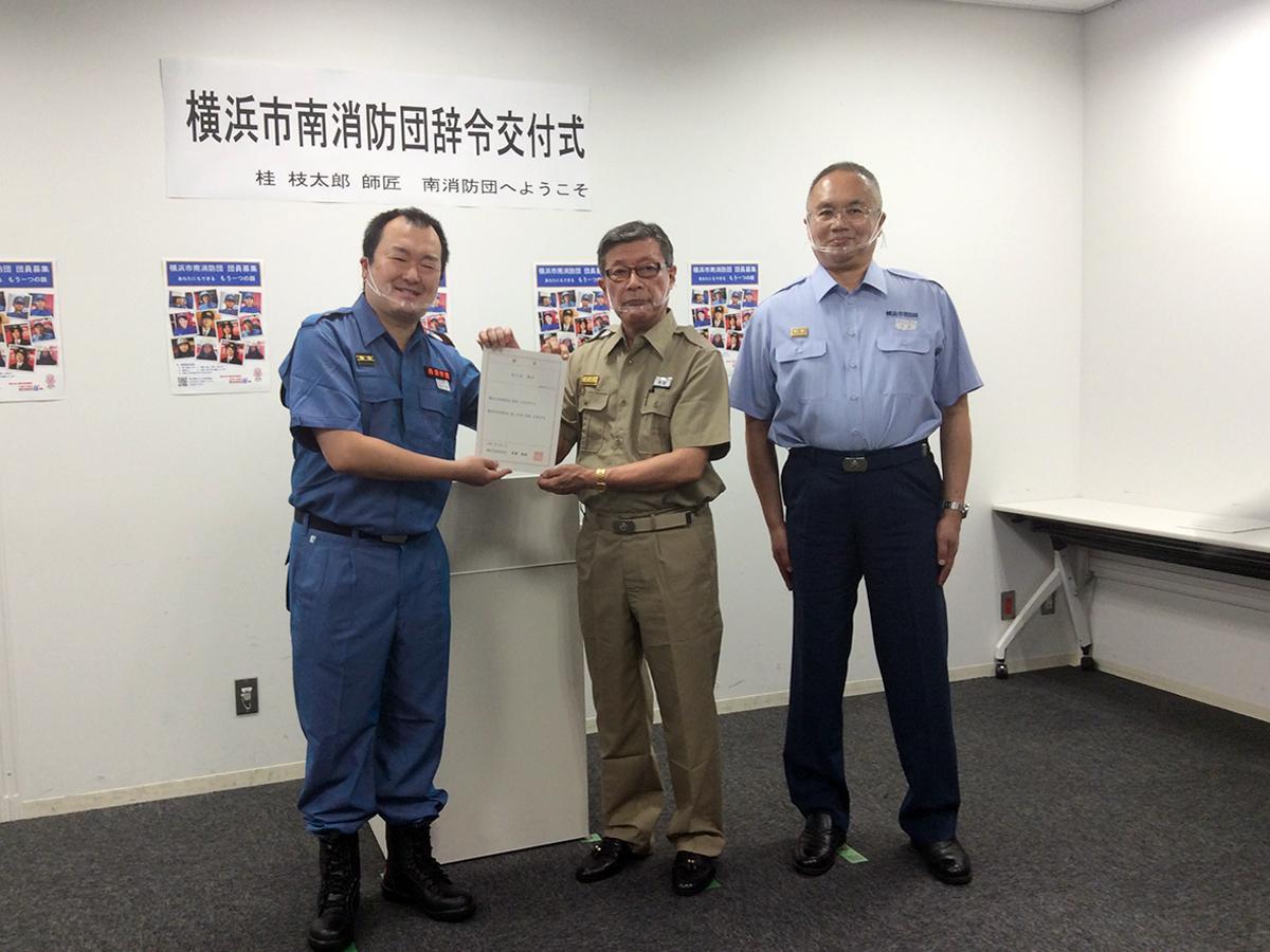団長の有賀さん(中央)から辞令を受けた桂枝太郎さん。活動着を初めて着用して式に臨んだ。