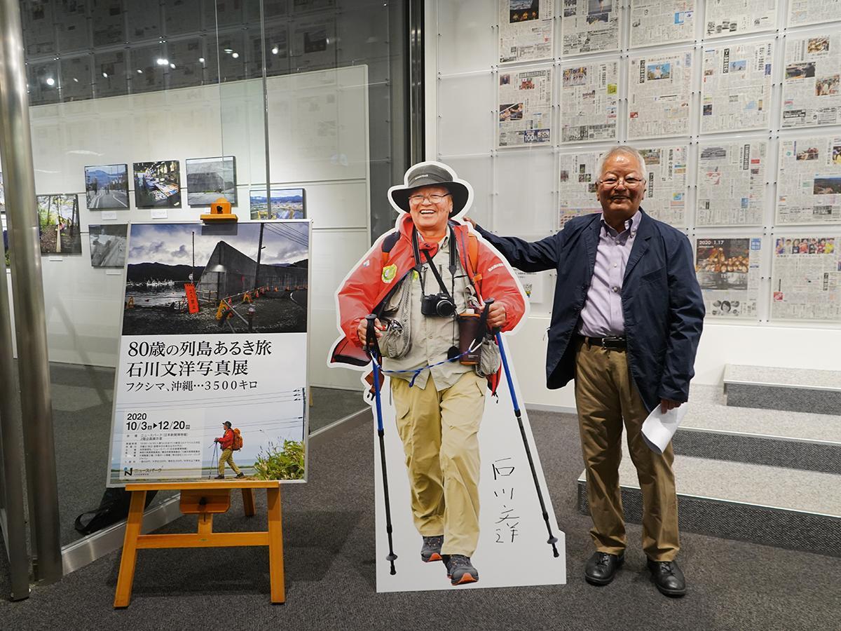 写真展会場入り口で、自身の等身大のパネルの横に立つ石川文洋さん