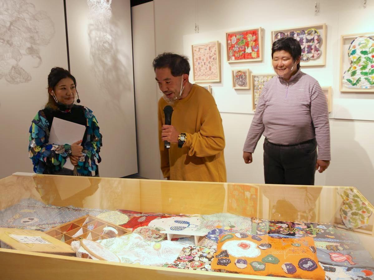 港南福祉ホームとミナ ペルホネンとのコラボ作品「sing a sewing」の展示について説明するホームのメンバーと総合ディレクターの栗栖良依さん(左)