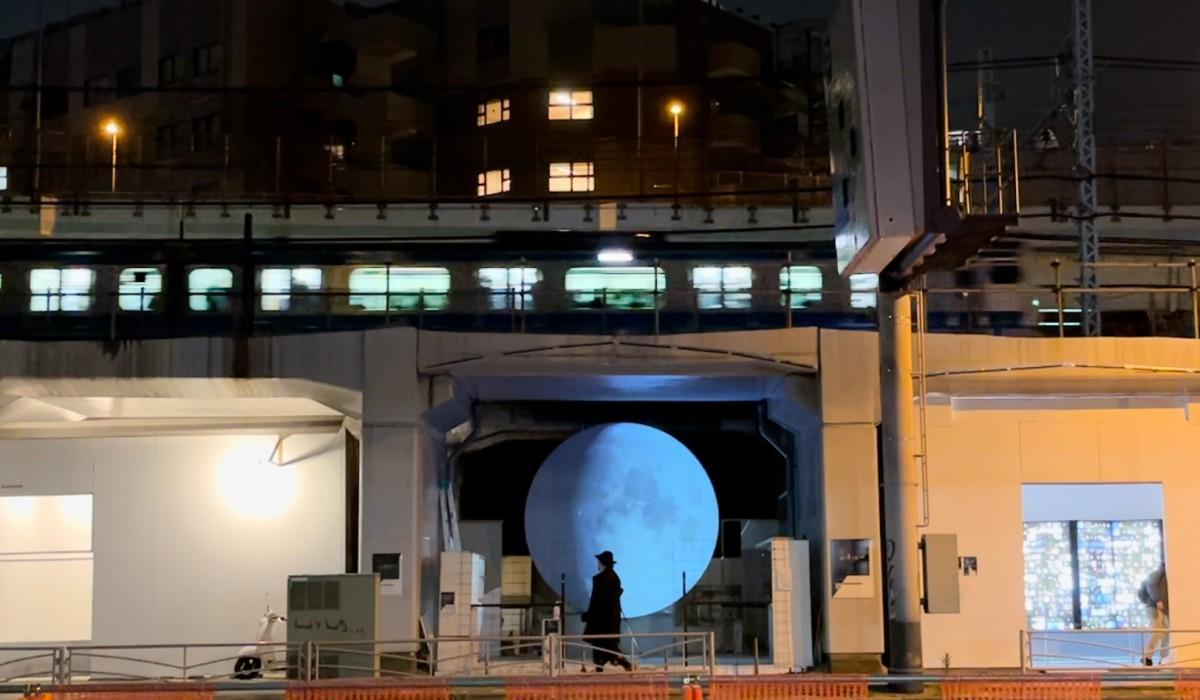 月の直径は約3.3メートル。廃線跡に平行してJR京浜東北線が走っており、大きな月を目前に見ながら、頭上に列車が走る音が聞こえると「銀河鉄道の走行音が聞こえたかのような感覚」という観覧者も。マントと帽子のシルエットは渡辺篤さん。