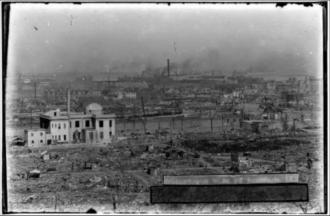 現在のJR桜木町駅周辺の様子をとらえた写真。「横浜市惨害全景(其貮)」西野写真館旧蔵関東大震災写真原板。伊勢山(現在の西区)から横浜市街地を俯瞰したパノラマ写真4枚のうちの1枚。