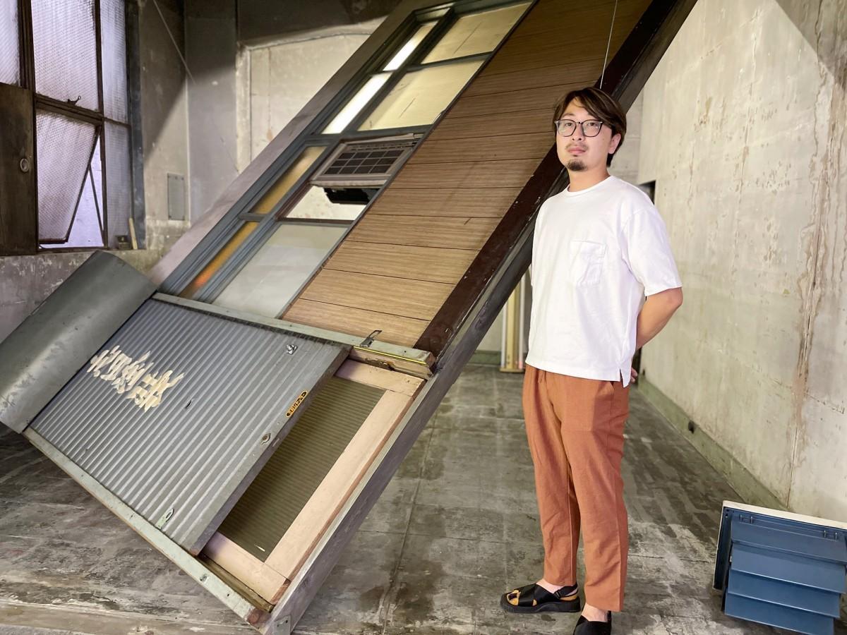 美術家の酒井一吉さん。個展「現れの場」では隣室の壁を一度分解して運びこみ、再度組み立てた。