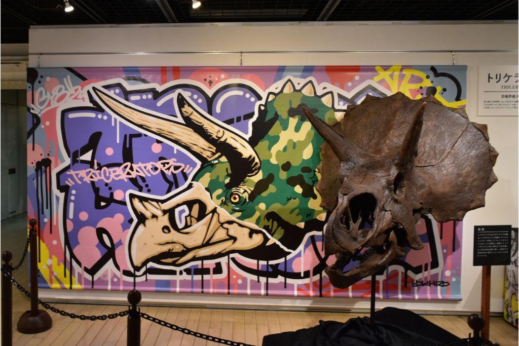 「トリケラトプス 頭骨」とストリートアーティストのYOICHIROさんによるオリジナル描き下ろしの恐竜アート「トリケラトプス」