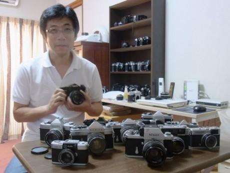 たくさんの年代フィルムカメラを前にする渥美さん