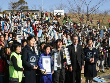 認定証を受け取った小学生の代表とギネスワールドレコーズ社の担当者、鈴木康友市長