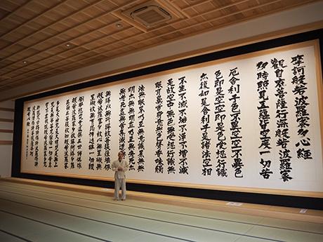 副住職の木宮行志さんと横16メートルの「世界一大きな般若心経」