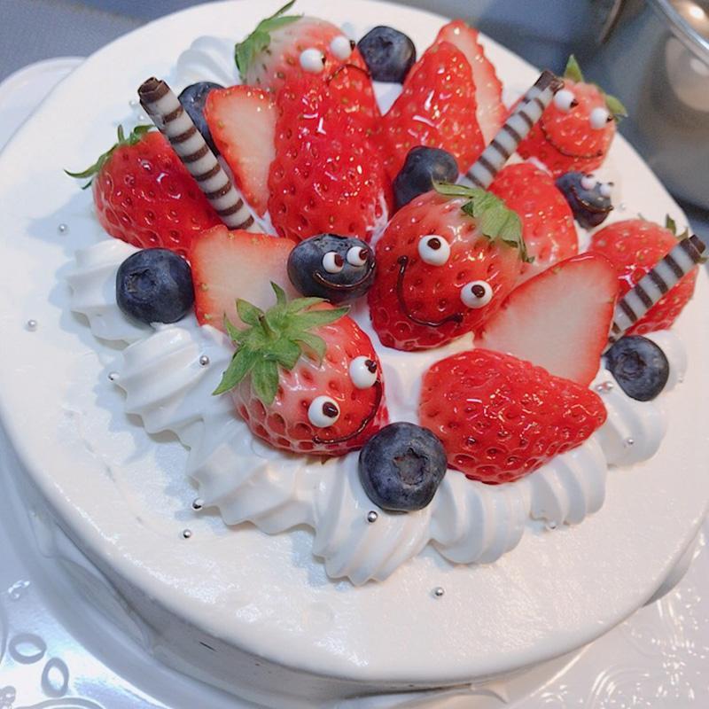 イチゴに顔を描き可愛らしくデコレーションしたケーキ