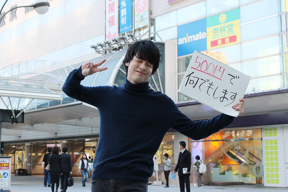 浜松駅前で「500円で何でもします。」のスケッチボードを掲げる林さん