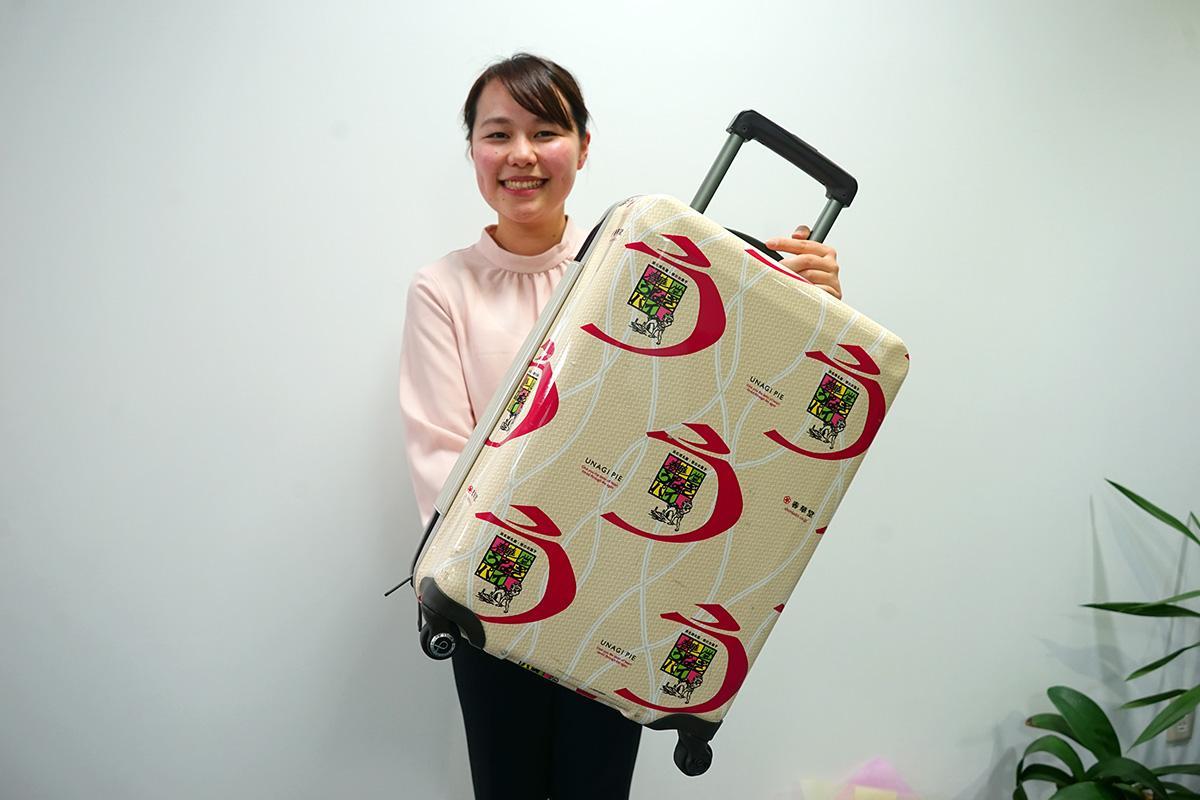 プレゼントのキャリーケースを持つ、広報の手嶋千恵さん