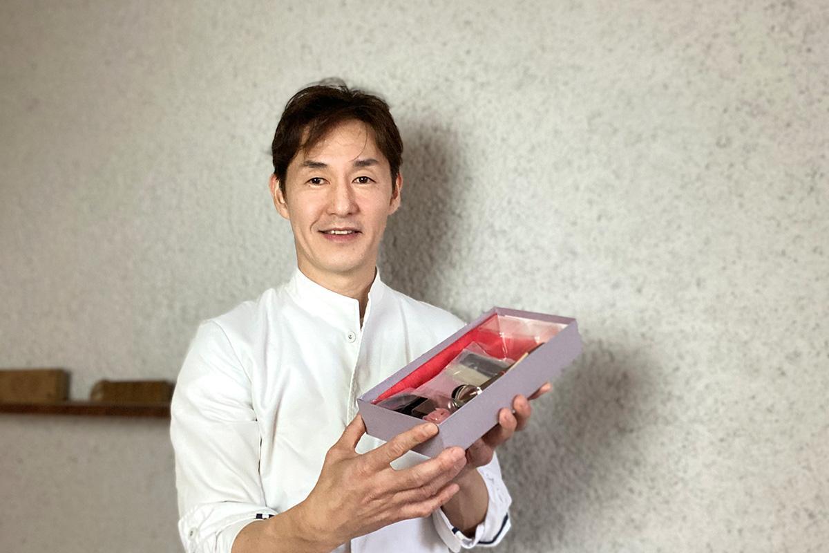 和菓子手作りキットを持つ、社長の内田弘守さん