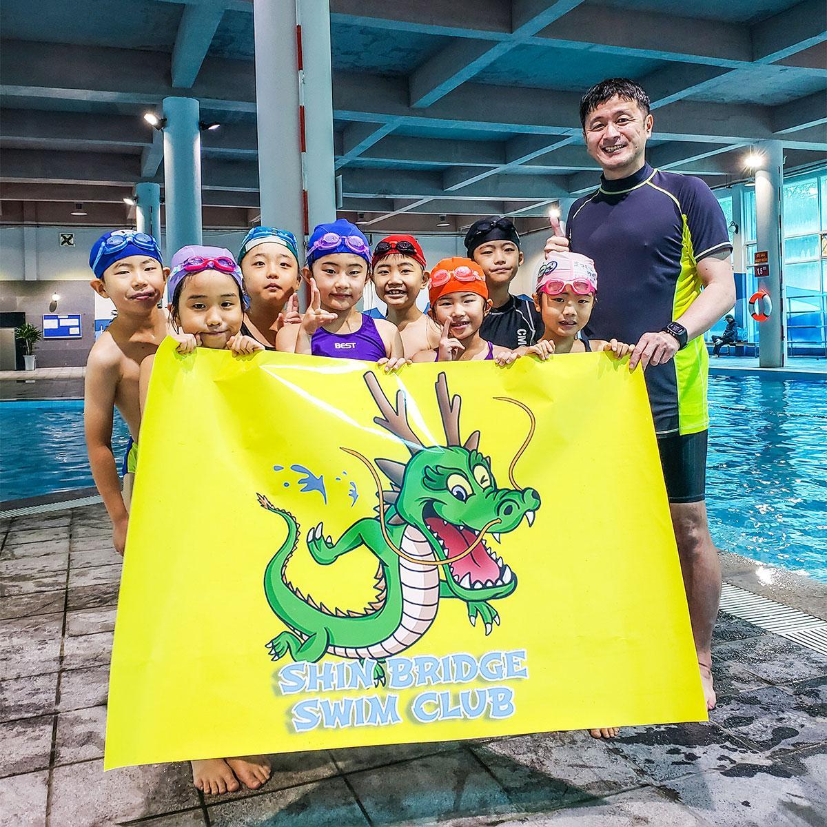 コーチの桑原伸一郎さんと水泳を学ぶ子どもたち