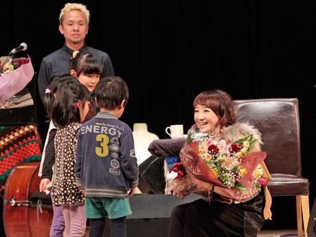 小学校の担任教諭や親せきの子どもたちから花束を受け取る「たむらぱん」