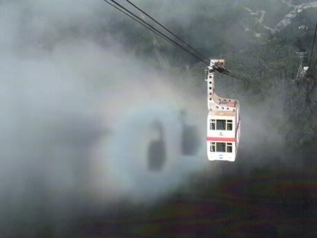 虹色の光輪に囲まれ霧に浮かび上がる2台のゴンドラの影(写真提供=谷脇勲さん)