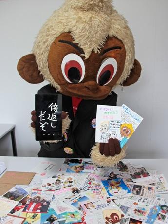 全国から届いた年賀状を前に喜ぶお猿のくぅ