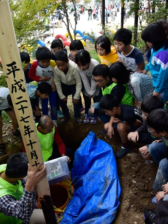 思い出の品を詰めたタイムカプセルを見守る3年2組の児童たち
