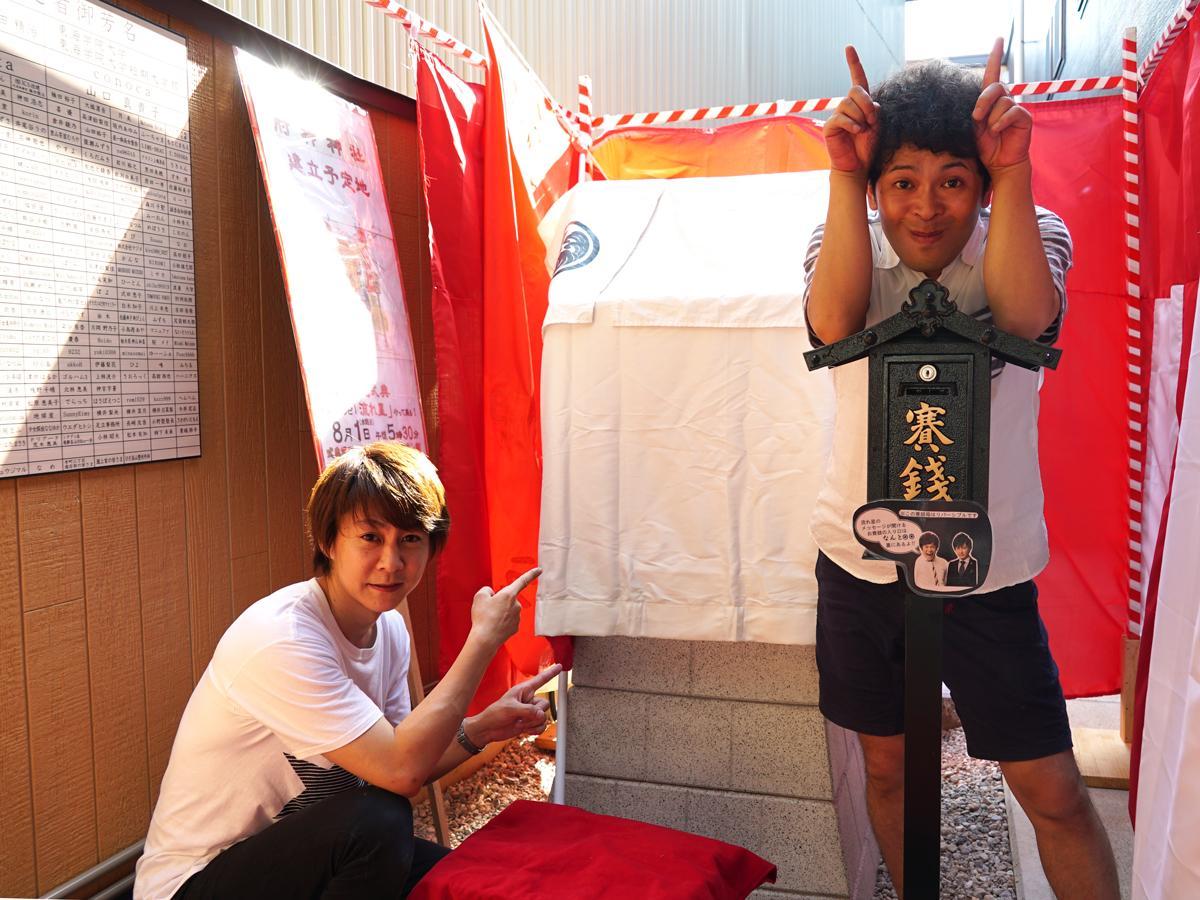 お披露目を待つ肘神神社前で来場を呼び掛ける「流れ星」の2人。敷地内の左壁にはクラウドファンディングによる寄進者の芳名板も(7月31日撮影)
