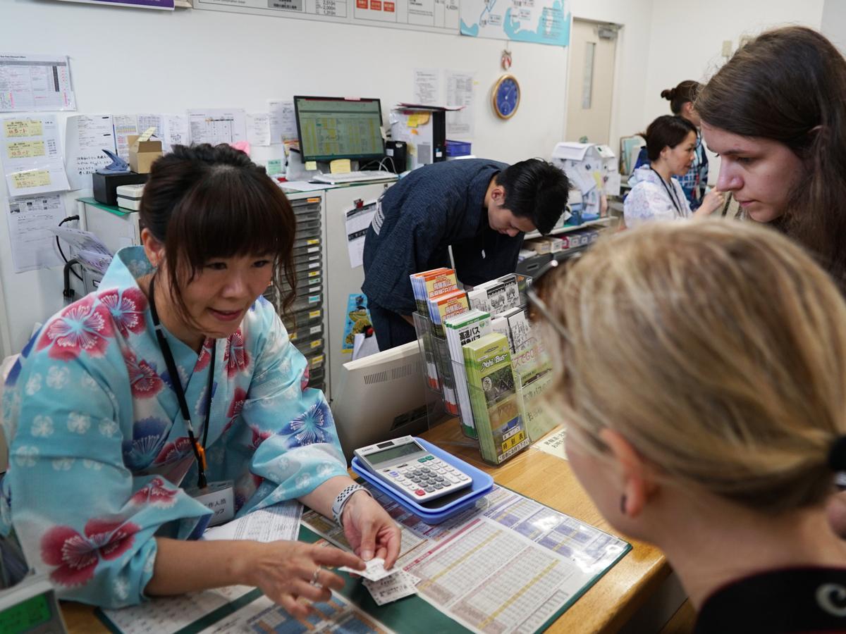 浴衣姿で外国人旅行者の対応に当たる中国人スタッフのソウ・シホさん(左)(高山濃飛バスセンターで)