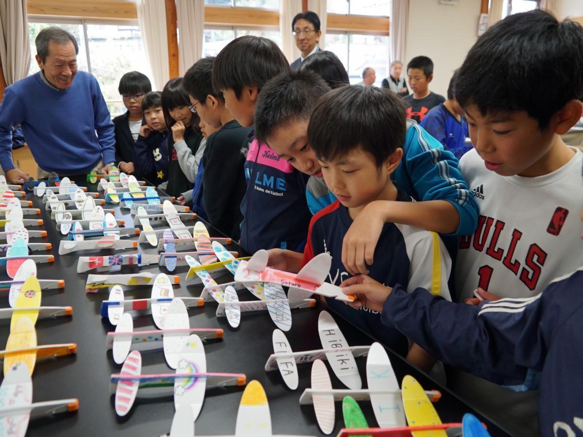 完成した紙飛行機を前に荒木さん(左)と児童たち