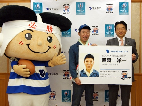 「モノづくり東大阪応援大使」の名刺パネルを受け取る「モンスターエンジン」の西森洋一さん