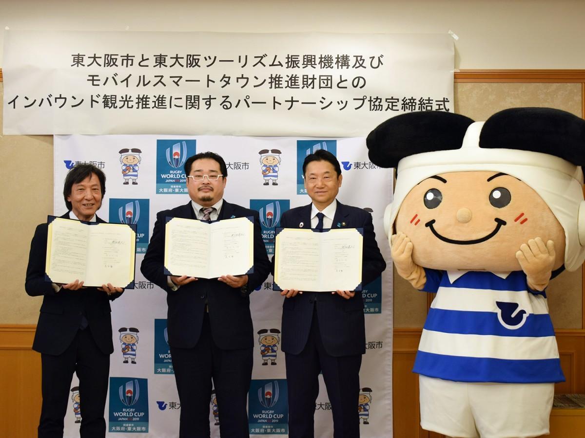 写真左から、東大阪ツーリズム振興機構・清水洋一郎代表理事、モバイルスマートタウン推進財団・落合正和専務理事、野田義和東大阪市長