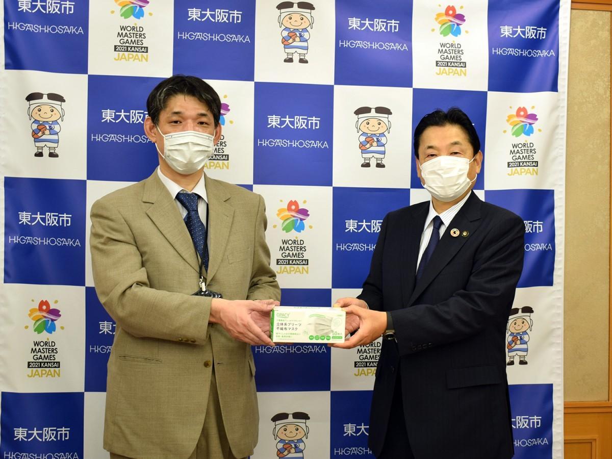 マスクを寄贈したドクターズファーマシーの藤澤英義社長(写真左)と野田義和東大阪市長