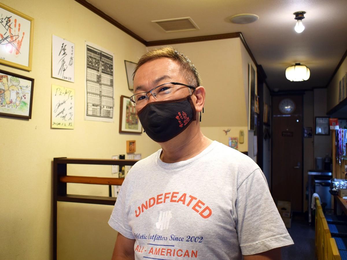オリジナルマスクを着ける店主の田中裕之さん