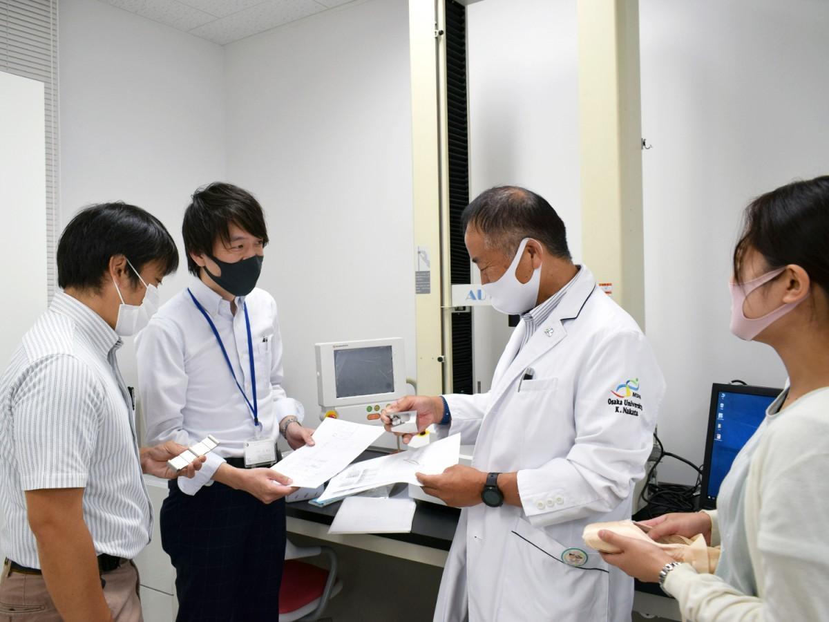 大阪大学大学院医学系研究科で引張試験機の特注治具の打ち合わせをする辻さん(左から2番目)