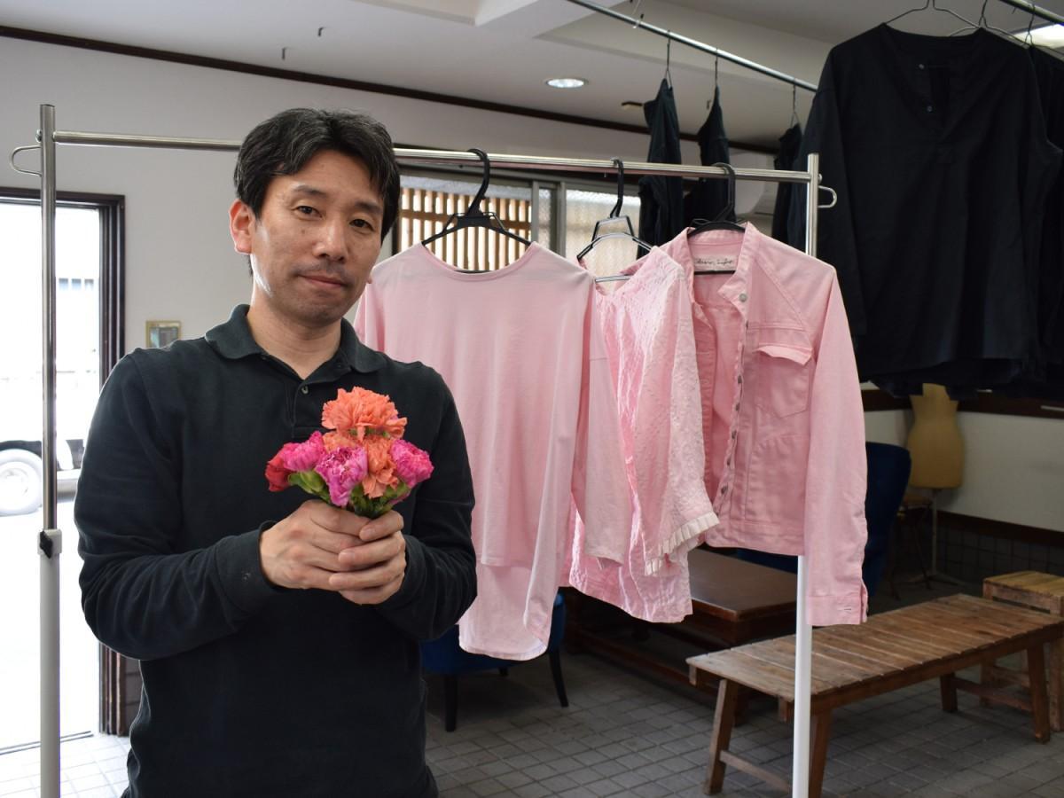 福井プレスの福井伸社長と廃棄予定のカーネーションで染めたピンクの衣類
