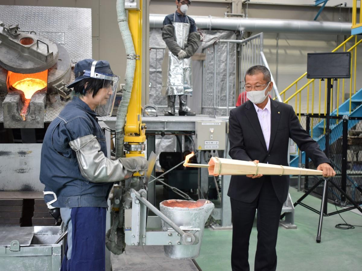 電業の濱谷社長が溶解炉から火を採り出す