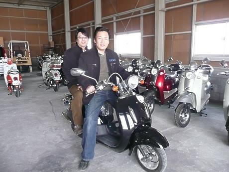 2人乗りが可能な電動スクーター「エルドラド」にまたがる有元浩明社長