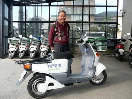 配達用にカゴと荷台を取り付けた電動スクーター「レコロ カーゴ」と神戸新聞田寺専売所の畑尾さん。